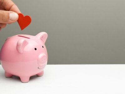 Photo : tirelire cochon dans laquelle une main dépose un coeur
