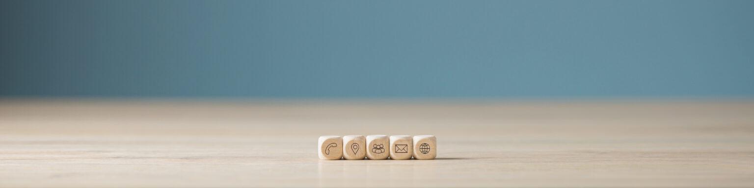 Photo de 5 dés dont les faces représentent un téléphone, une position, des membres, une adresse, Internet